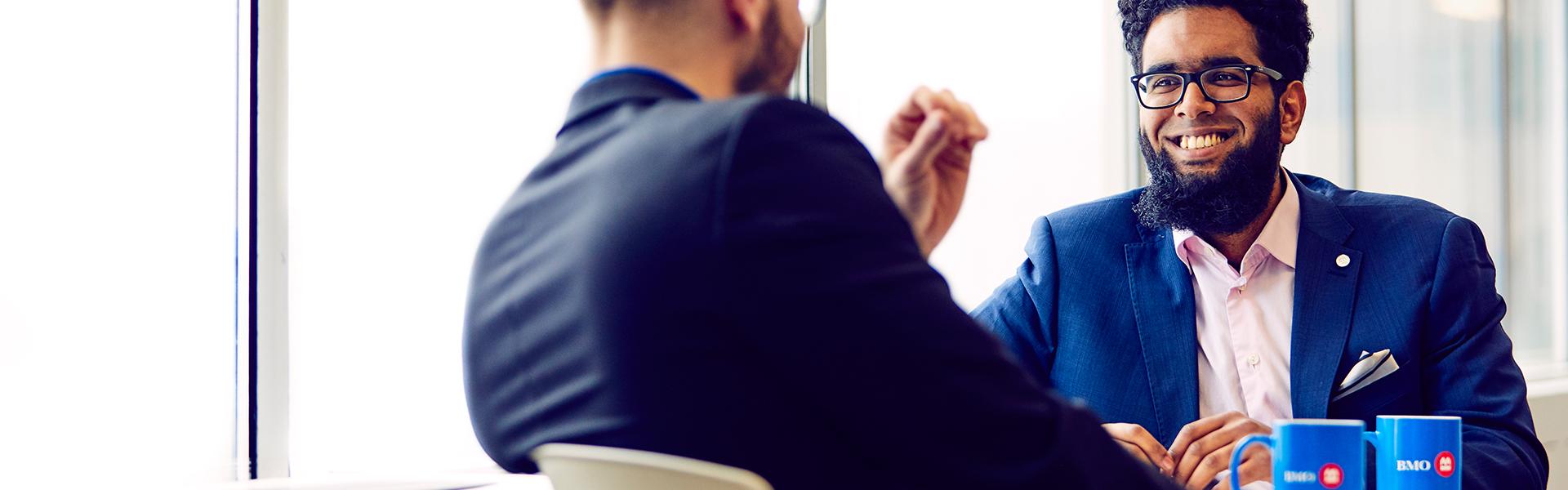 Two male coworkers having a coffee break.