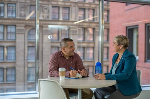 Two employees at a table having a discussion.