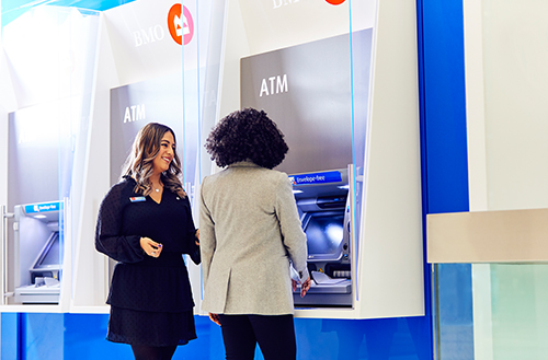 Female employee smiling to another female in front of ATM