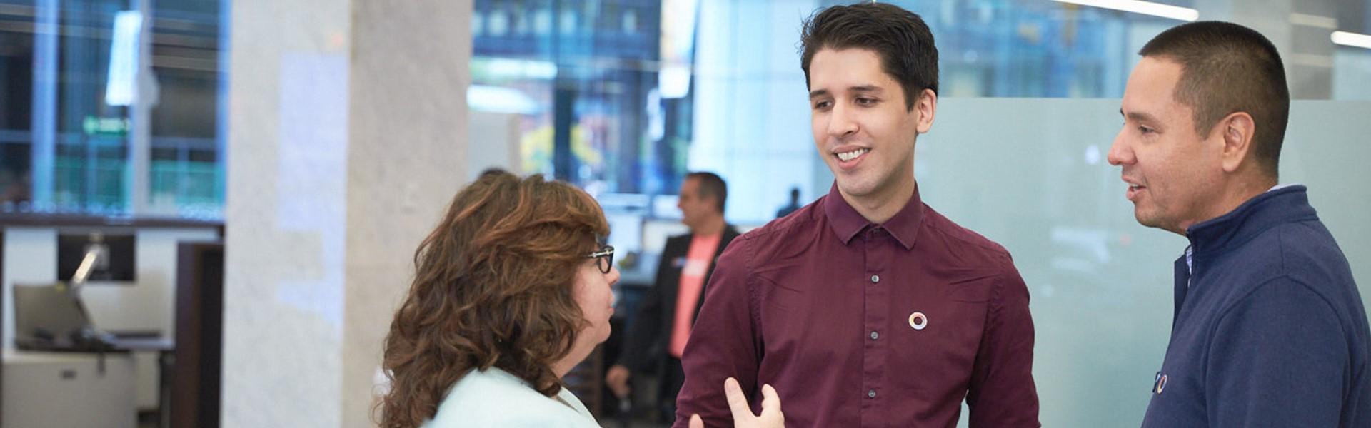 Three employees having a standing conversation.
