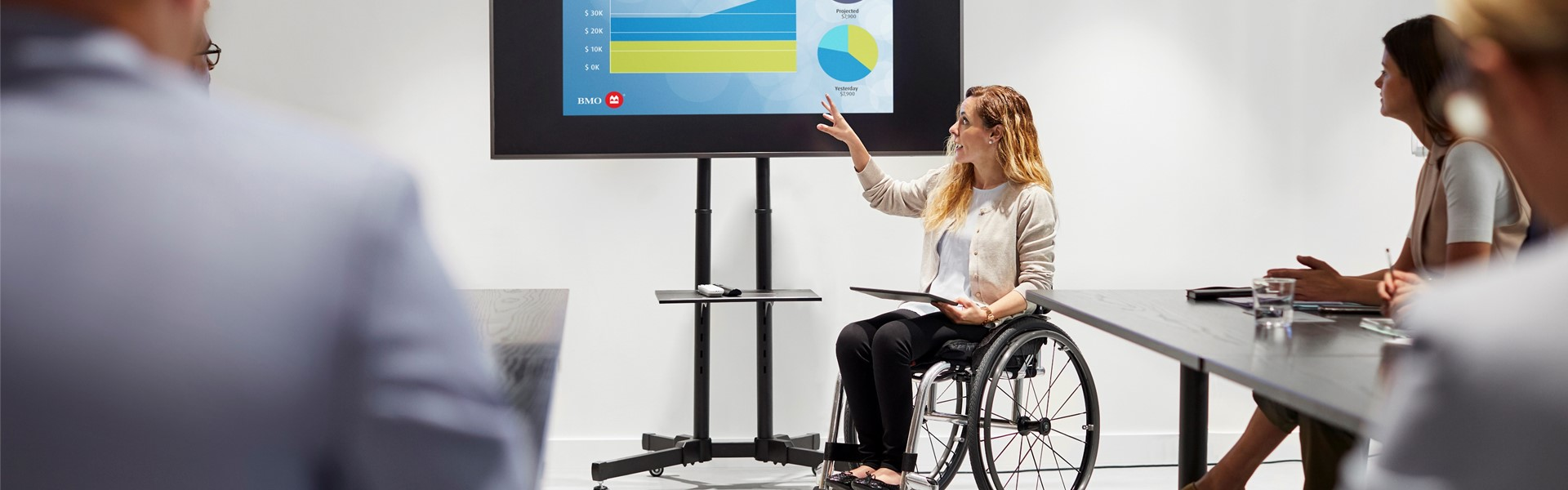 Female employee in wheelchair presenting on a large screen.