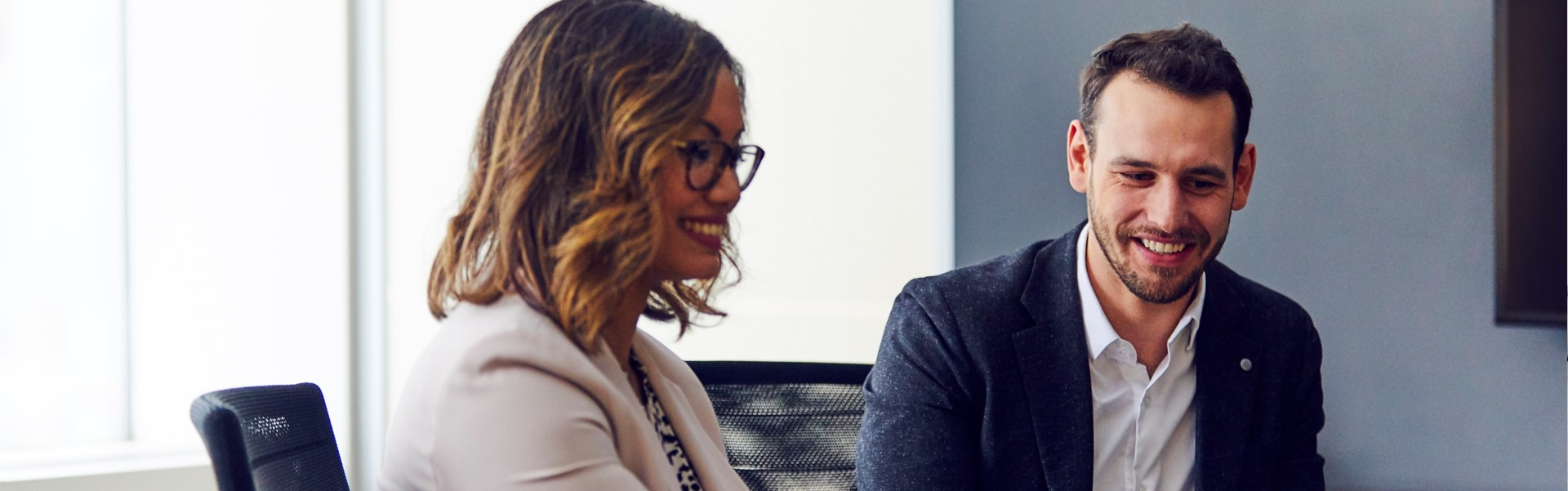 Deux employés qui discutent lors d'une réunion.