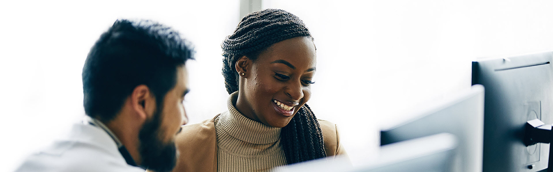 Female smiling and looking at computer.