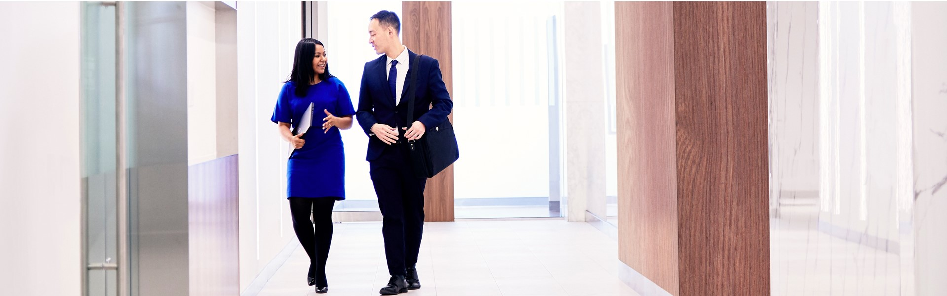 Two employees walk along a corridor in the bank lobby.