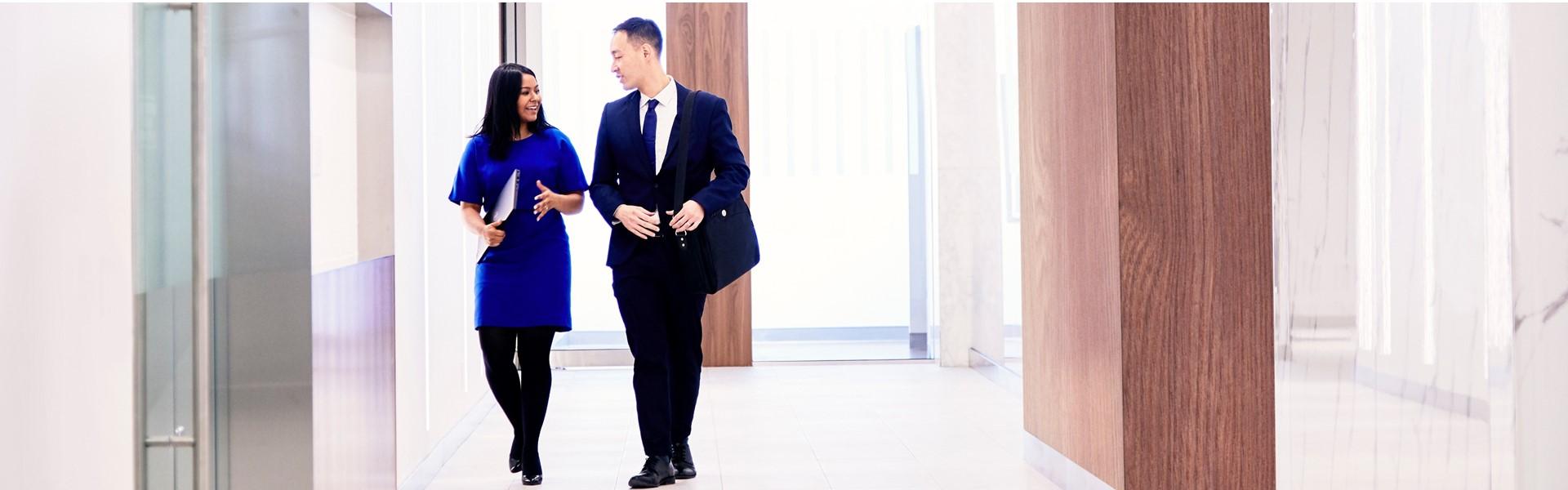 Deux employés qui marchent dans un corridor de l'aire d'accueil de la Banque.