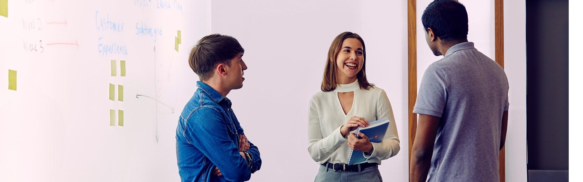 Trois employés discutant dans la salle de conférence