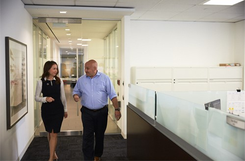 Two employees walking down a corridor