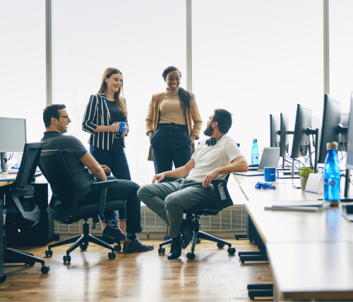 Groupe d'employés qui discutent à leur bureau.
