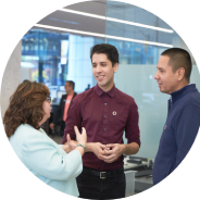 Three employees standing having conversation