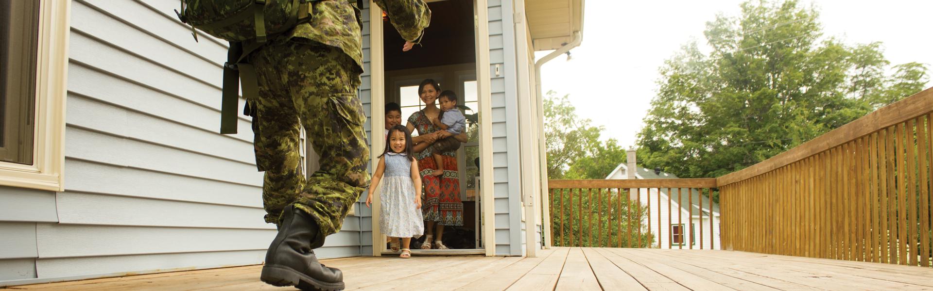 Soldat de retour à la maison qui salue sa famille.