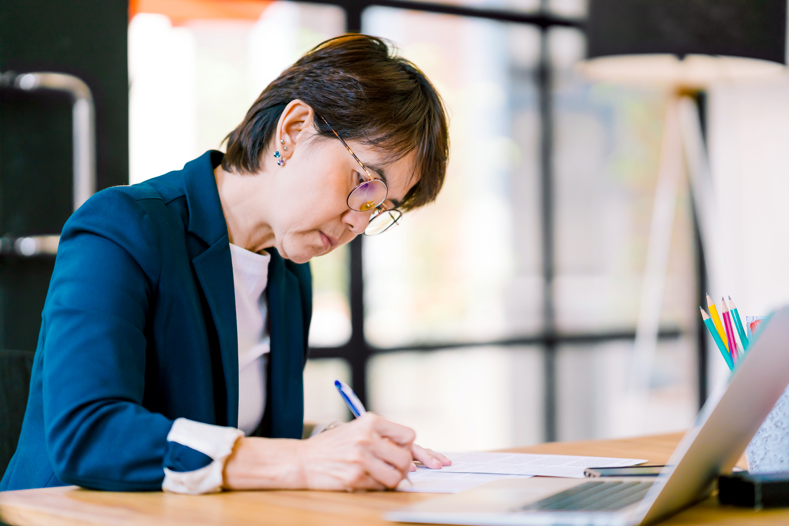 woman in suit at desk writing