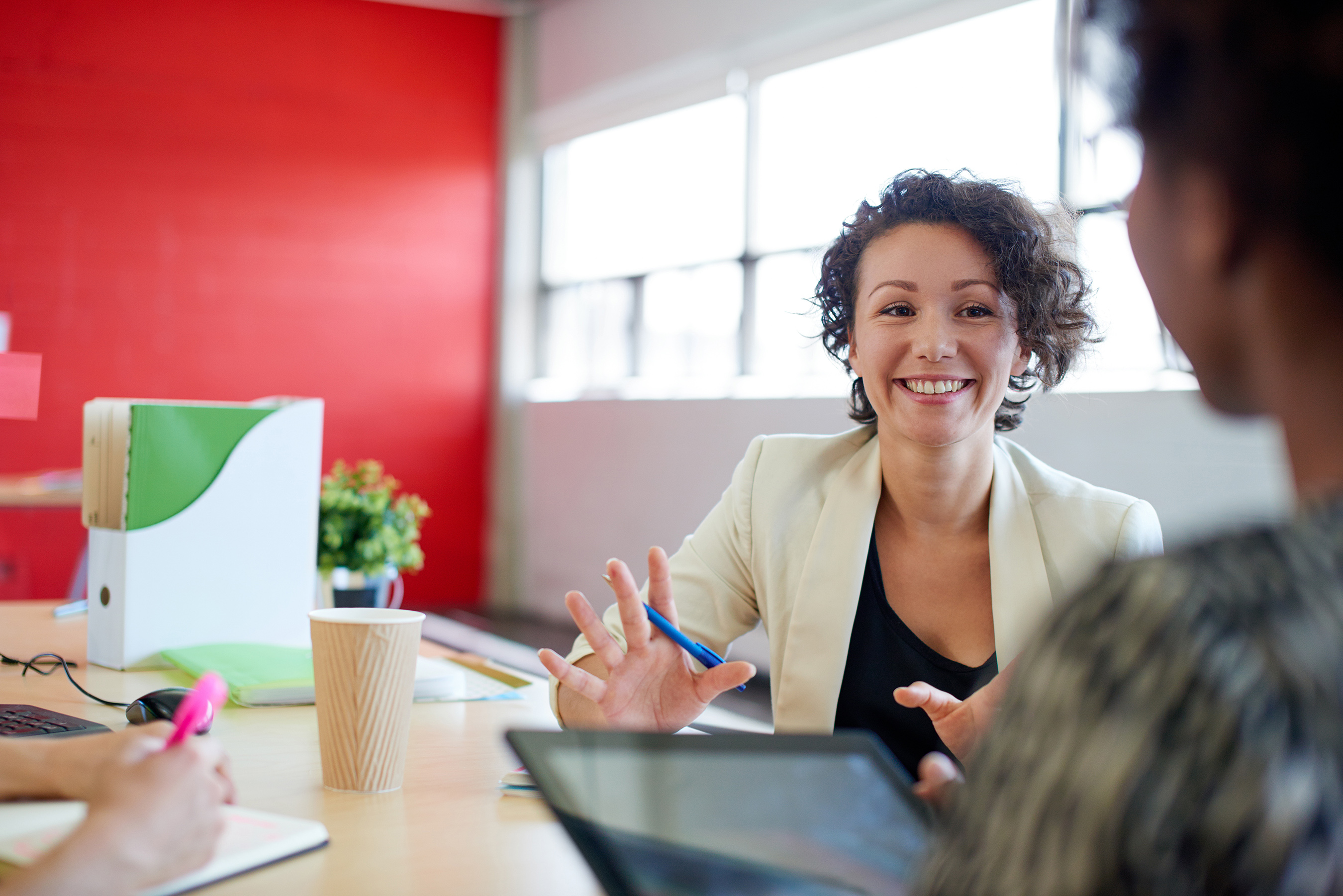 woman at desk smiling at another woman with tablet