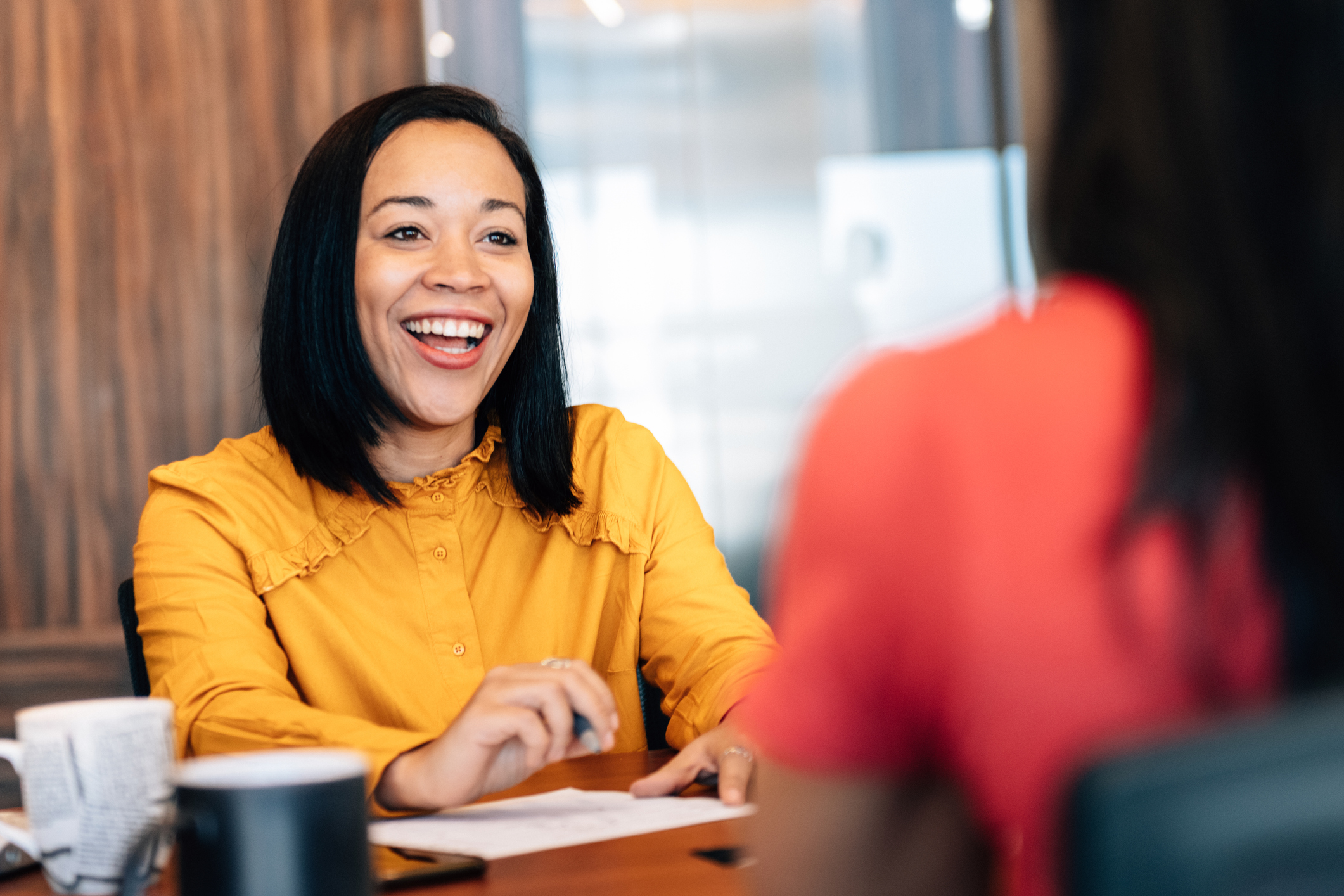 woman at desk smiling at another woman
