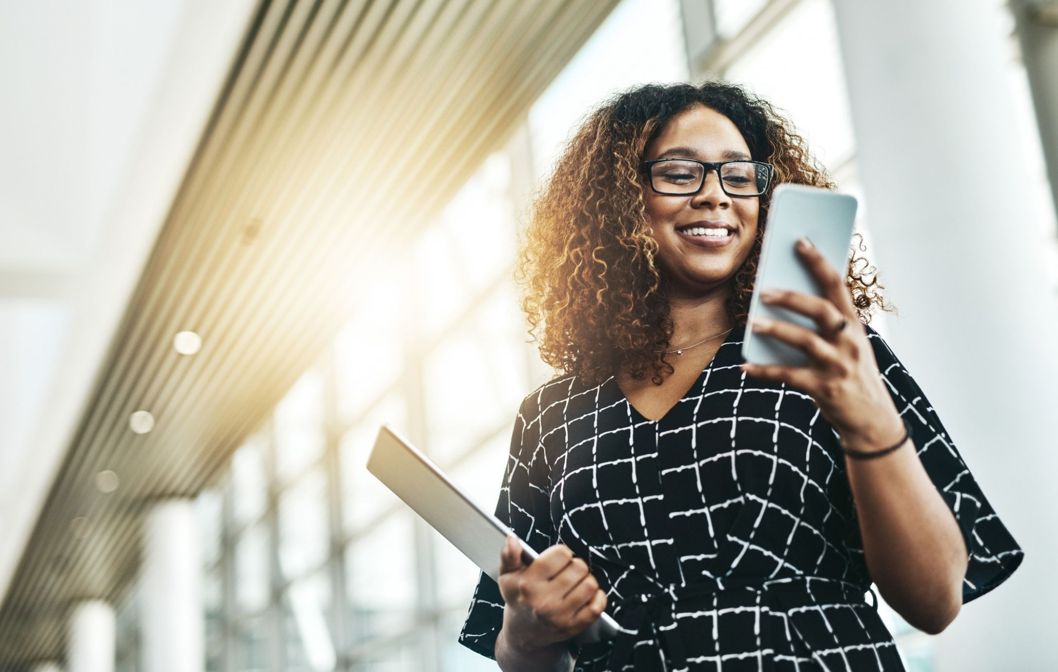 Woman smiling at phone carrying tablet