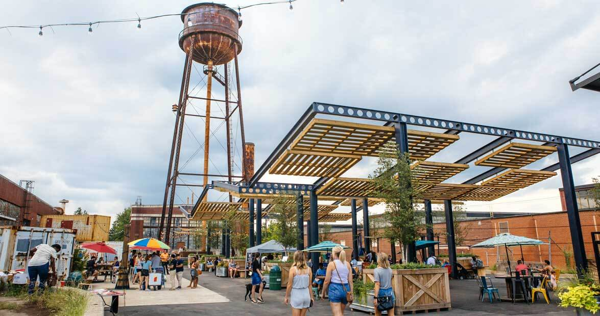 Outdoor view of Camp North End water tower and visitors enjoying the courtyard