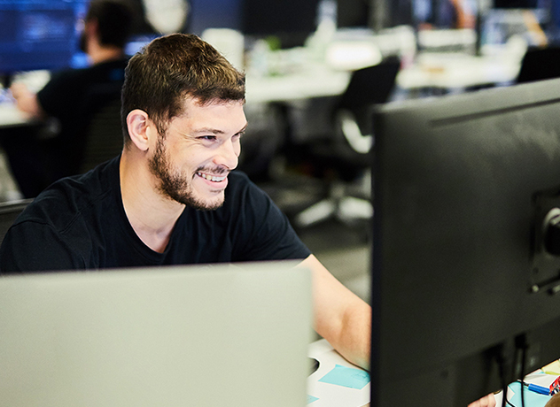 One smiling Chewy team member at their desk, looking at their screen