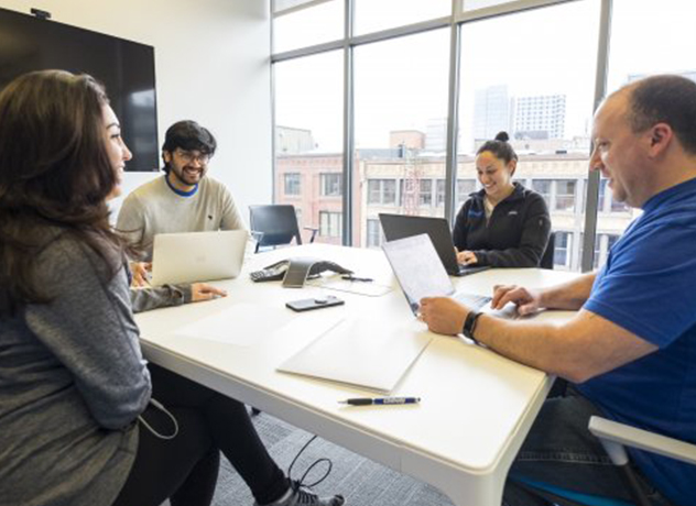 A group of Chewy team members meeting around an office table with a view of the city outside the windows