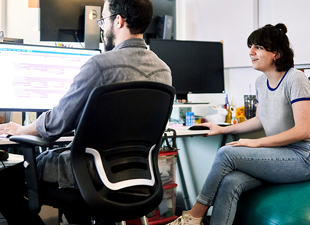 Two Chewy team members looking at a computer screen, one sitting in an office chair and one on a medicine ball