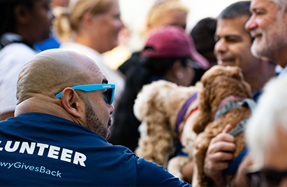 A Chewy team member with blue sunglasses at a volunteer event, surrounded by dogs and other people