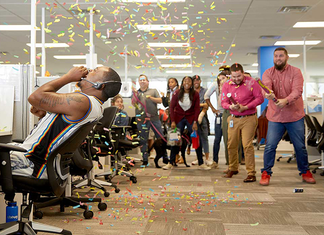 A group of Chewy team members surprising a fellow team member with a confetti cannon blast in celebration of a milestone