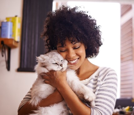 A smiling Chewy team member hugging a white and fluffy cat