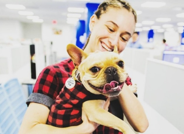 A Chewy team member and their dog wearing matching flannel shirts, smiling at the camera