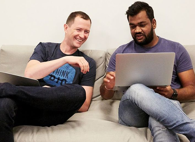 Two Chewy team members sitting on a couch looking at a laptop screen