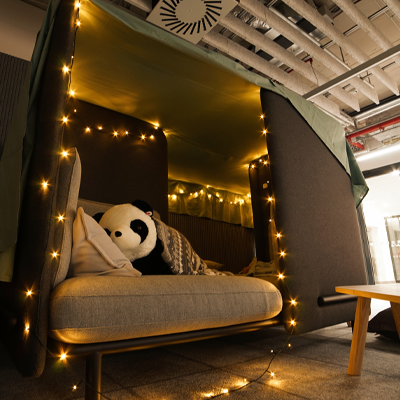 A Panda stuffed toy lounging on a comfy couch with string lights in the Prague Office