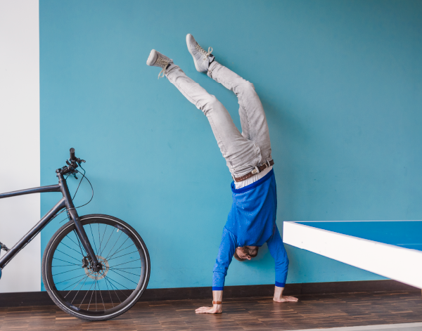 Upside down handstand next to bike and ping pong table with blue background