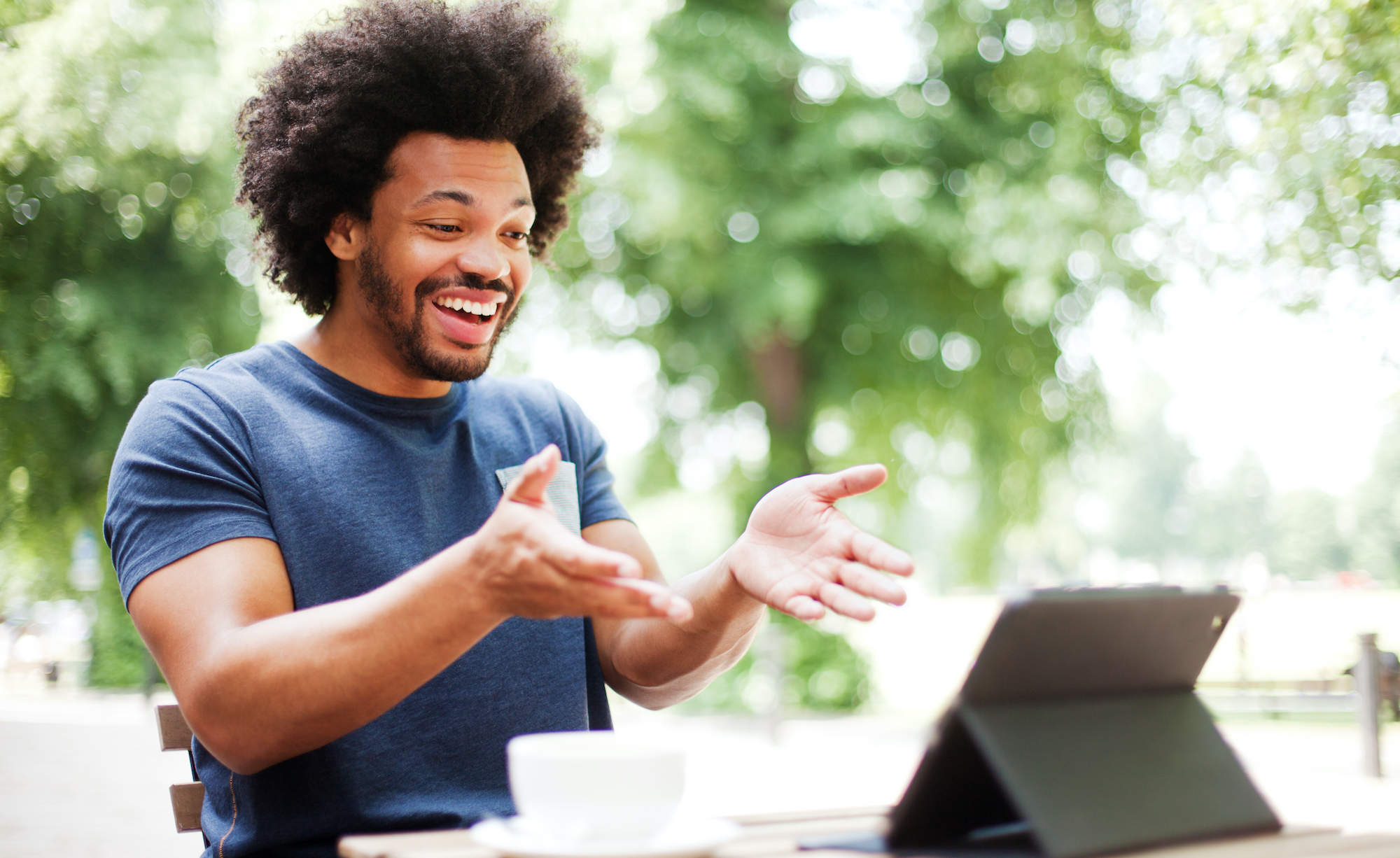 Man laughing outside looking at tablet during virtual meeting