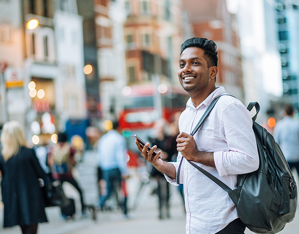 Young professional with backpack holding phone in the city