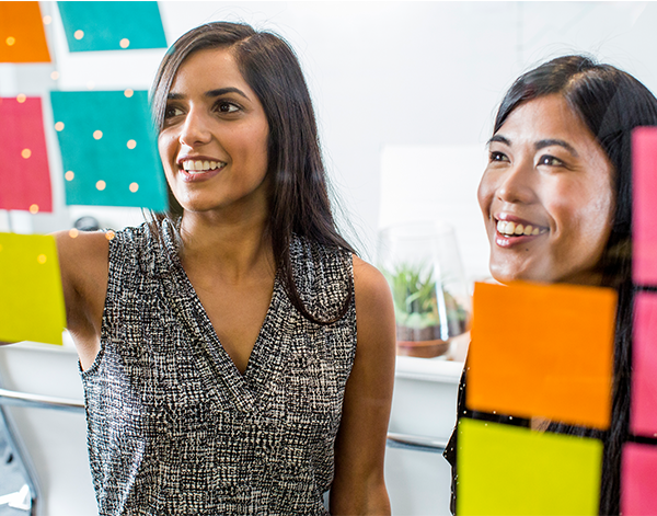 Two women working with sticky notes on a glass window to collaborate