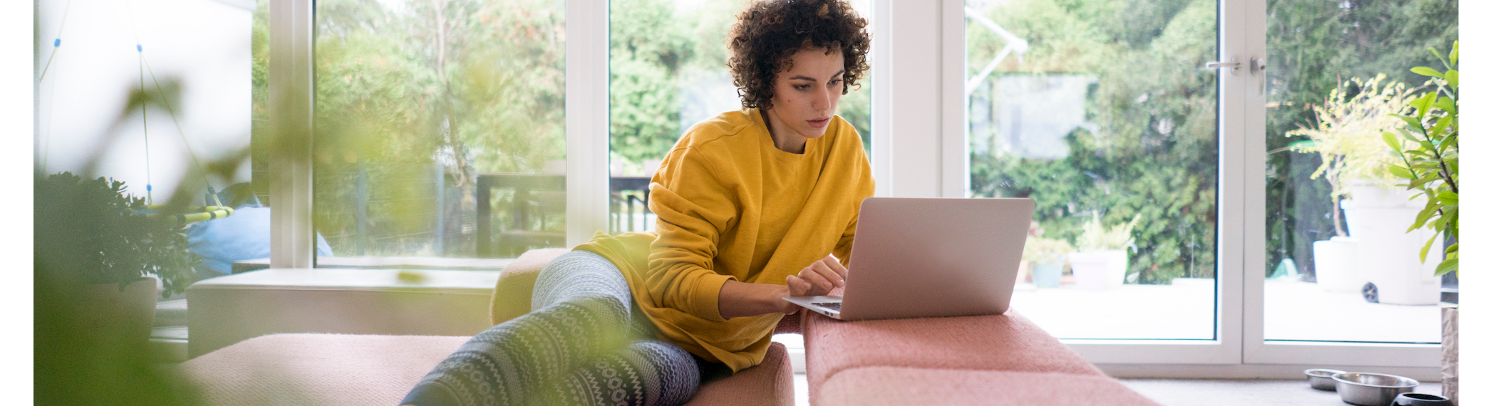 Woman sitting in living room, searching with laptop