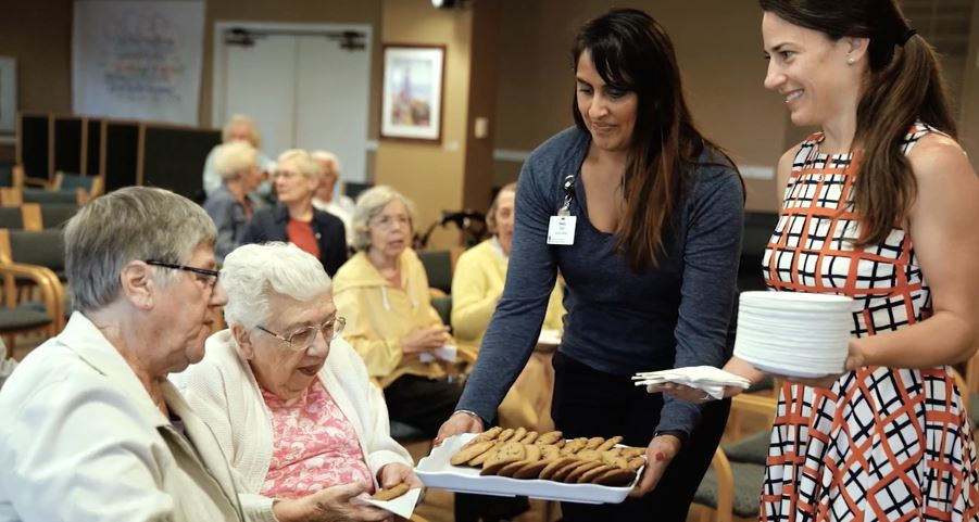 an image of two employees serving residents
