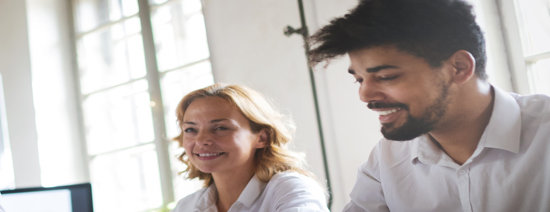 two people smiling in a meeting