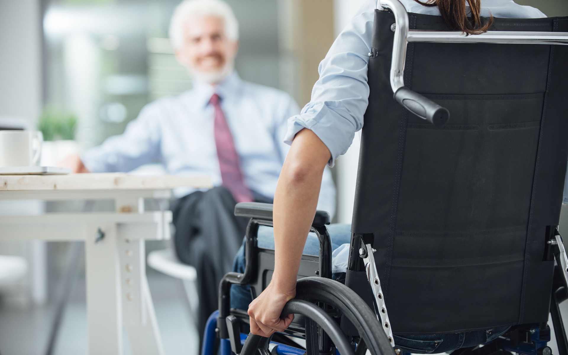 two people talking, one in a wheelchair.