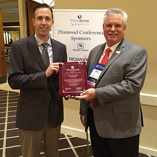 Photograph of Trojan Technologies associates holding a award