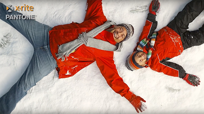 Photograph of two people making snow angels
