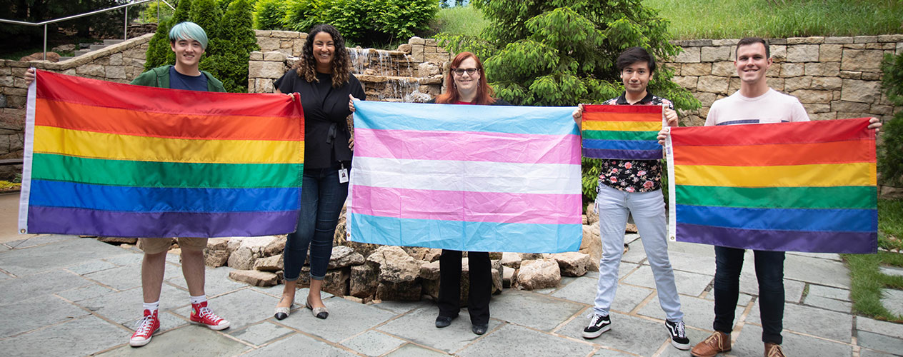 Five Garmin associates standing in courtyard holding lgbtq+ flags