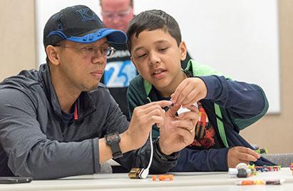 A Garmin associate helps a young boy build an engineering activity