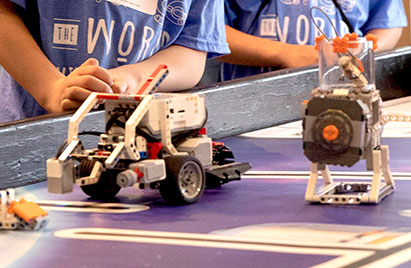 Two young boys in the background show off their robotics builds