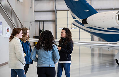 A Garmin associate speaks to three high school girls in front of an airplane in a hangar