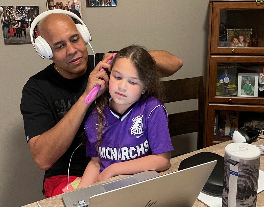 Charles McClendon working from home while also brushing his daughter's hair.