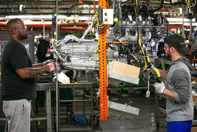 Employees working on an engine in a production plant.