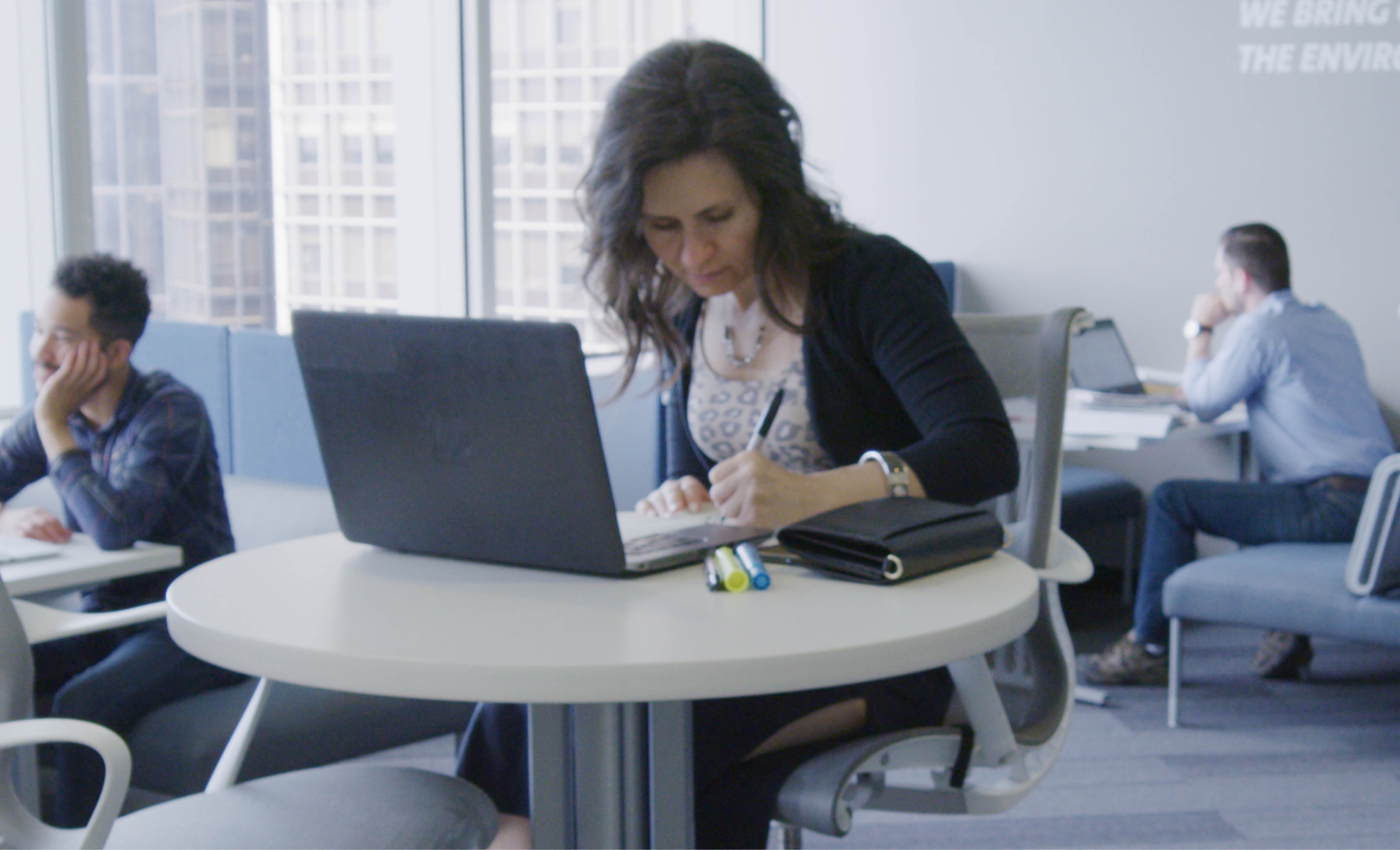 Woman working on a laptop in a shared workspace.