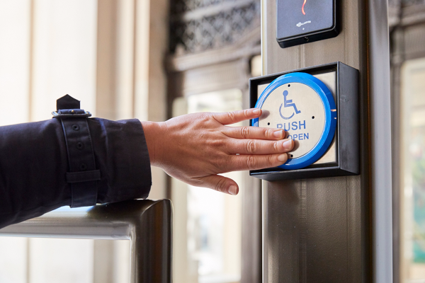 a person using an automatic door button