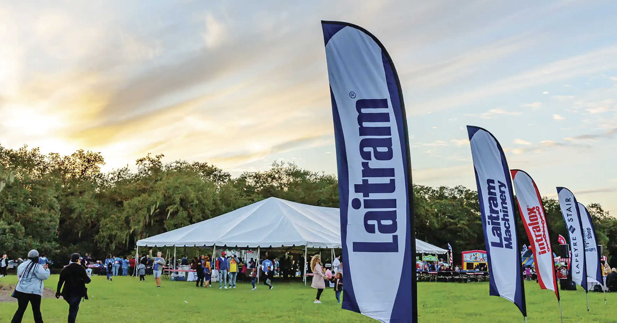 Laitram employee event on a grass field with a beautiful sunset