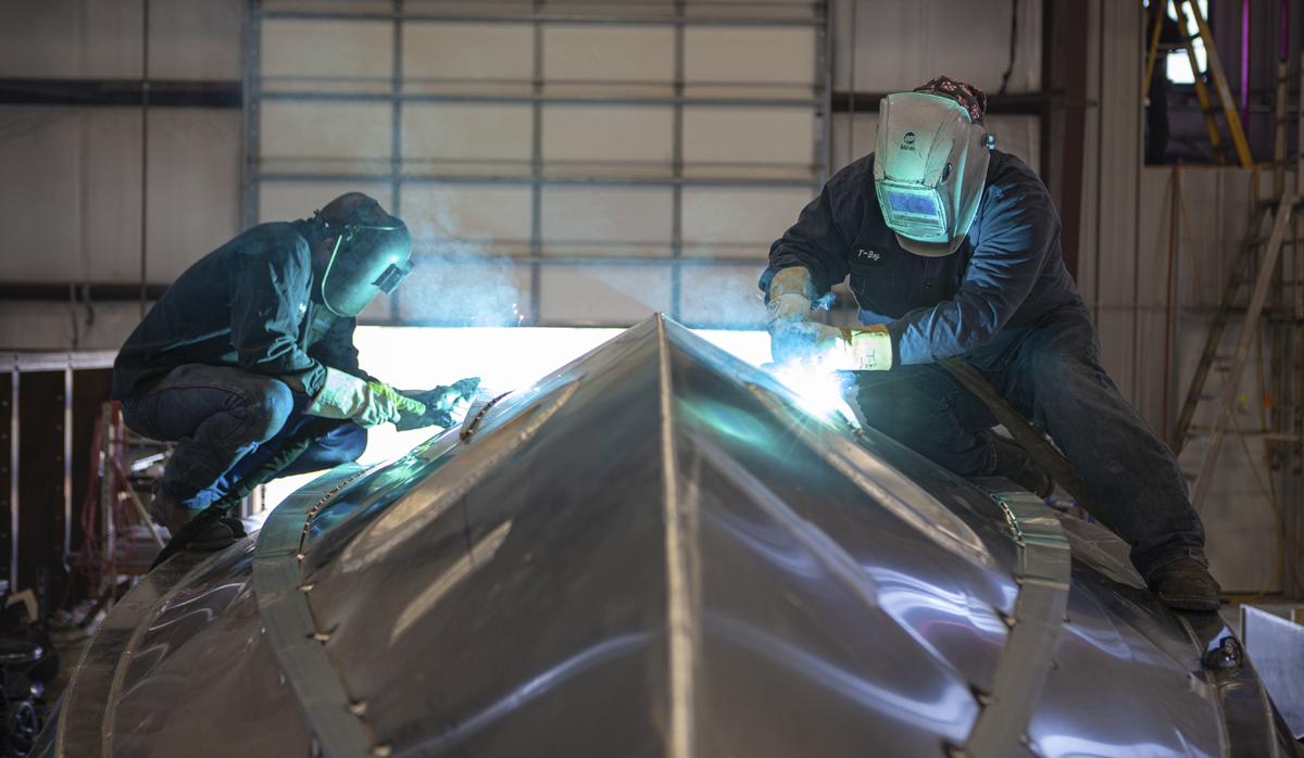 Welders welding a Metal Shark Boat together