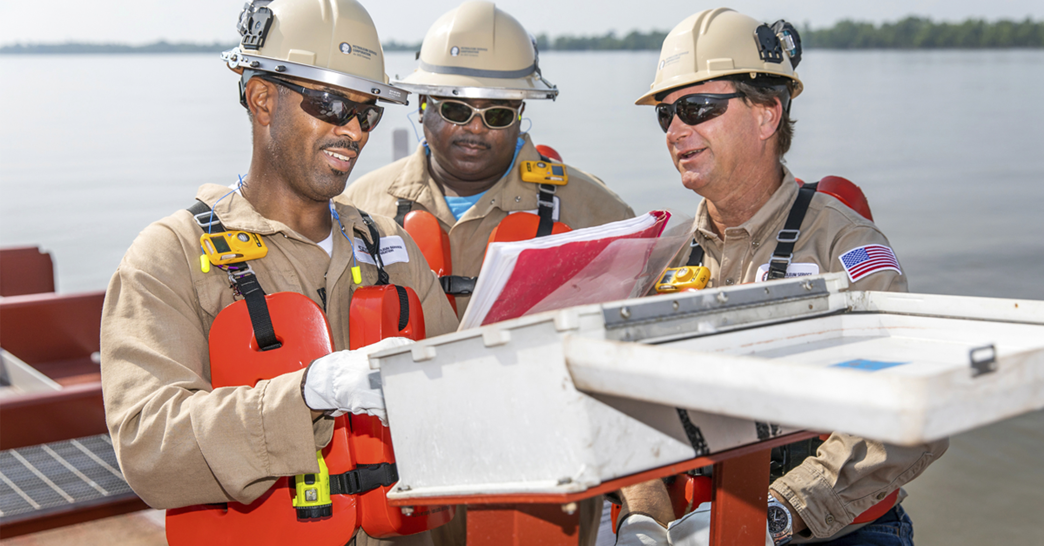 A picture of 3 PSC employees inspecting equipment
