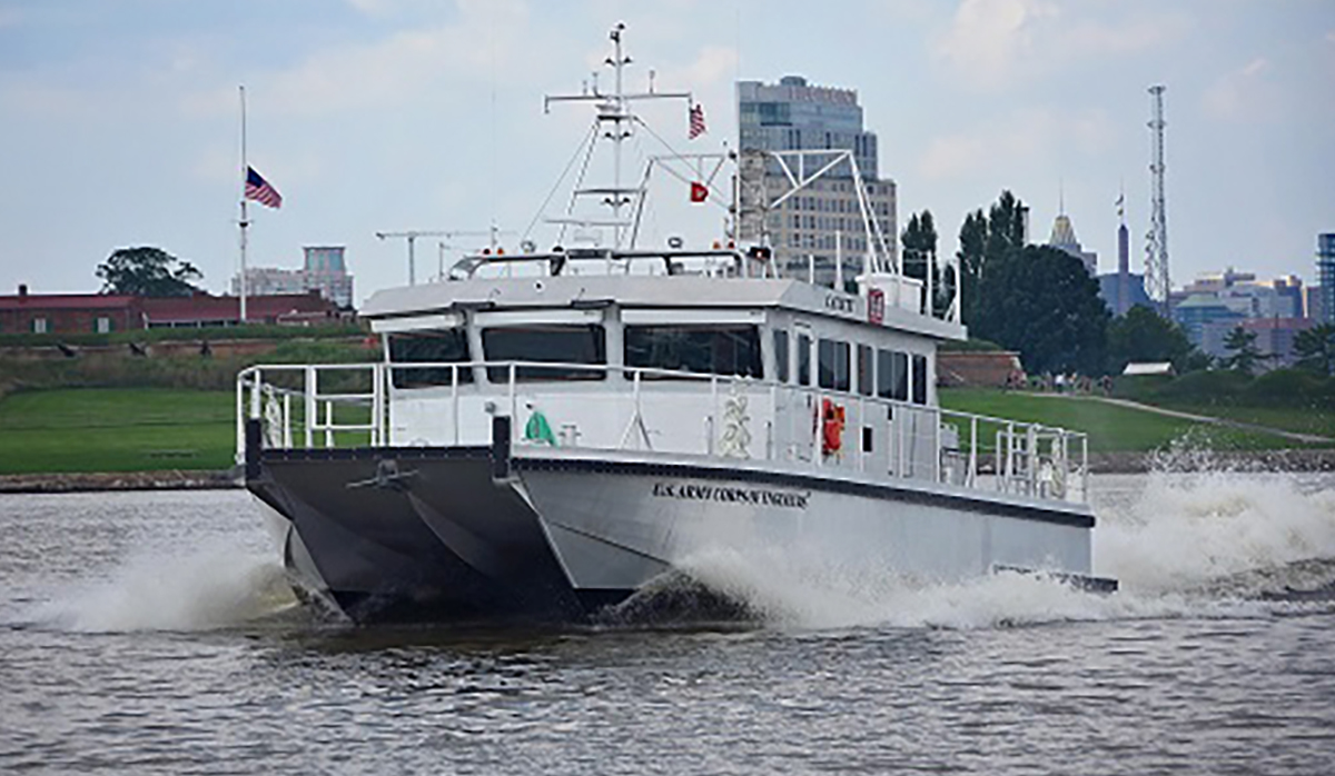 white ship steering through the water with buildings in the background